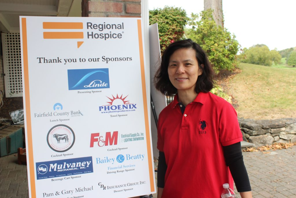 attendee standing next to regional hospice sponsor list