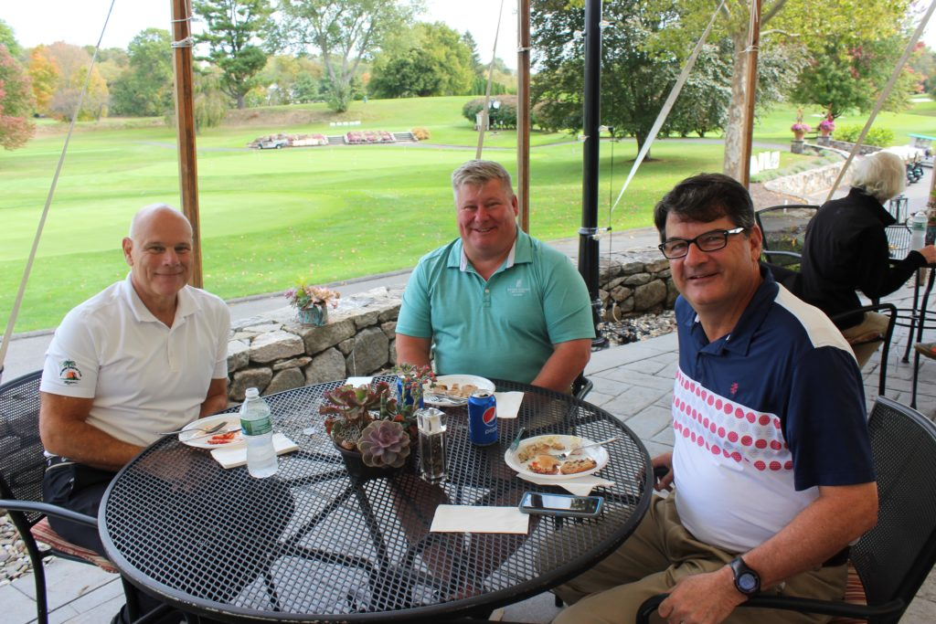 male golf attendees of regional annual golf tournament eating