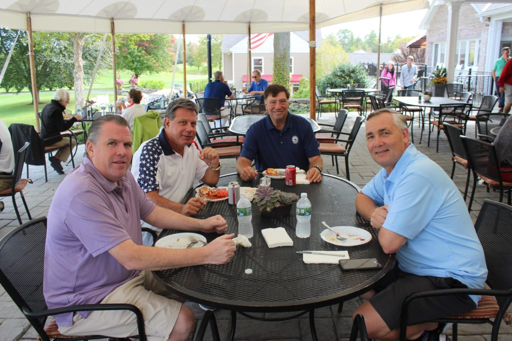 male golf attendees eating at annual golf tournament